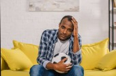 upset african american man holding soccer ball and looking at camera while sitting on couch at home