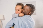 happy african american grandfather hugging adorable little grandson at home