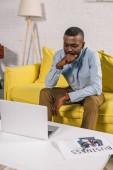 Fotografie fokussierte afroamerikanische Mann auf Sofa sitzen und mit Blick auf laptop