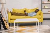 Fotografie älterer afrikanisch-amerikanischer Mann liegt auf Sofa und benutzt Laptop