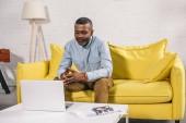Fotografie älterer afrikanisch-amerikanischer Mann sitzt auf Sofa und schaut auf Laptop