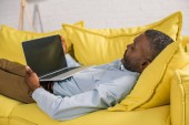 Fotografie Afrikanisch-amerikanischer Mann benutzt Laptop mit leerem Bildschirm, während er auf dem Sofa liegt