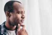Fotografia Ritratto del primo piano di pensoso uomo afroamericano con la mano sul mento che osserva via