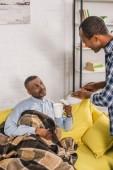 Fotografie adult son pouring tea to senior father sitting on sofa