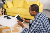 Fotografie high angle view of african american man using digital tablet with blank screen at home