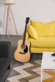 Photo acoustic guitar near cozy yellow couch in modern interior