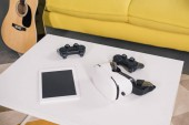 Fotografie close-up view of virtual reality headset, digital tablet with blank screen and joystick on table