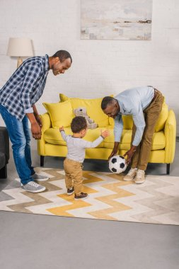 happy african american family playing with soccer ball at home