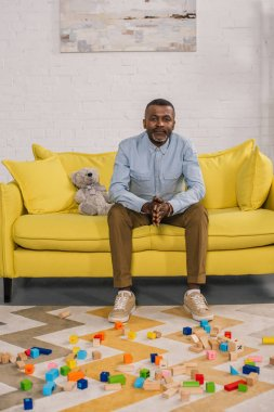 senior african american man looking at camera while sitting on yellow sofa in room with colorful blocks on carpet