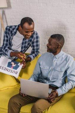 smiling young man with newspaper looking at senior father using laptop