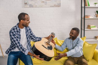 african american father and adult son holding acoustic guitar at home