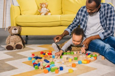 young father with cute little son playing with colorful blocks at home