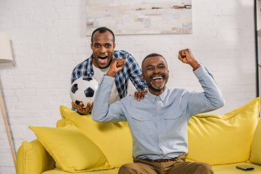 excited father and son with soccer ball triumphing and smiling at camera