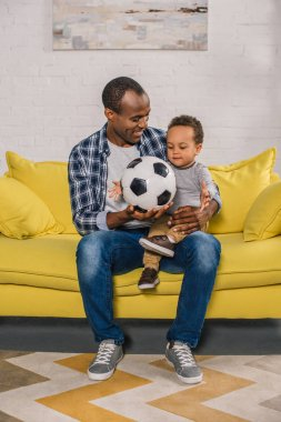 happy young father holding soccer ball and looking at cute smiling son