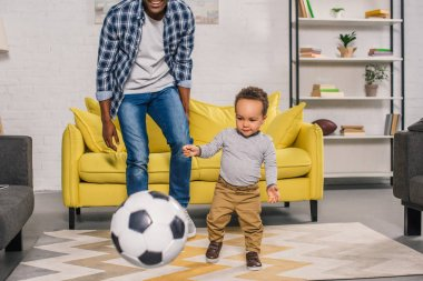 cropped shot of smiling father with cute little son playing with soccer ball at home