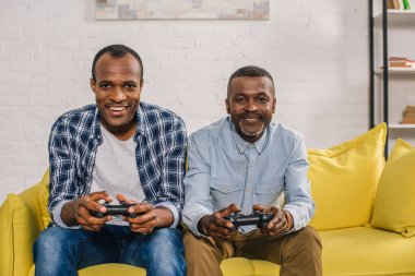 happy senior father and adult son using joysticks and smiling at camera