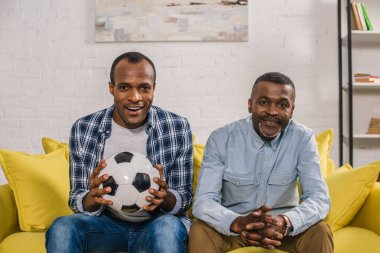 happy african american father with adult son holding soccer ball and smiling at camera at home