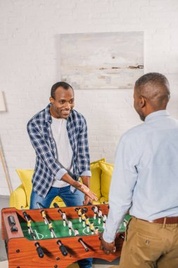 happy young man with senior father playing table football at home