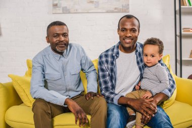 happy african american father, grandfather and child sitting together and looking at camera