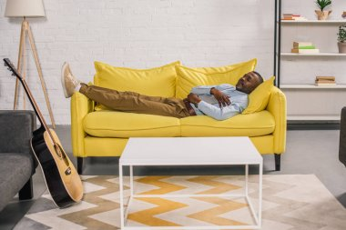 senior african american man sleeping on yellow couch at home