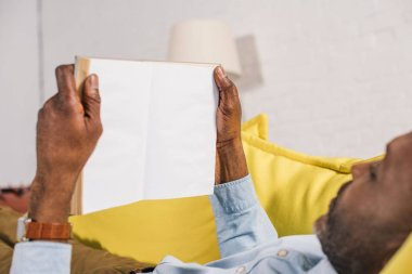 cropped shot of african american man reading book with blank pages while lying on couch