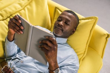 senior african american man lying on sofa and reading book