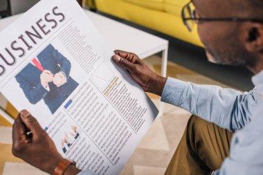 cropped shot of senior african american man in eyeglasses reading business newspaper