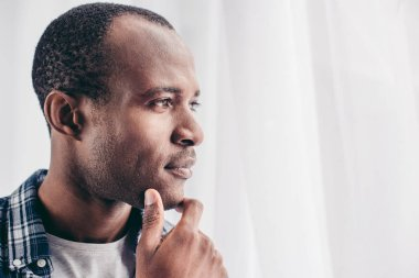 close-up portrait of pensive african american man with hand on chin looking away