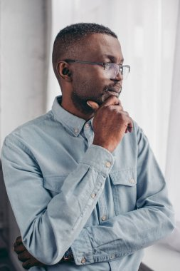 pensive senior african american man in eyeglasses standing with hand on chin and looking at window