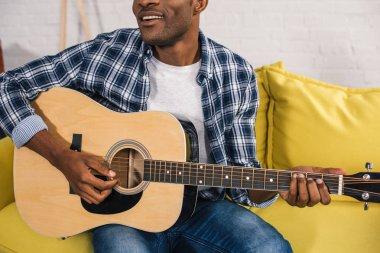 cropped shot of smiling african american man playing acoustic guitar at home