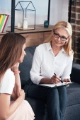 stressed woman sitting on session with female therapist at office