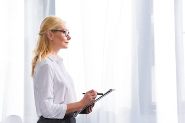 side view of female psychologist in eyeglasses writing in clipboard