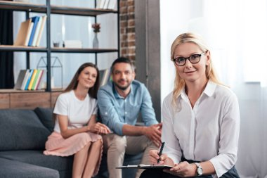female counselor writing in clipboard and looking at camera while happy family sitting behind on sofa in office