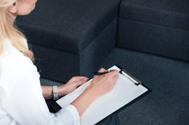 cropped image of female counselor writing in empty clipboard during therapy session in office