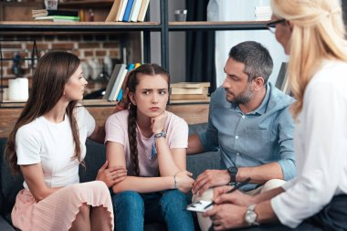 parents cheering up daughter on therapy session by female counselor in office