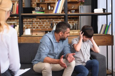 father with wide arms talking to little son in headphones on family therapy session by female counselor