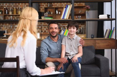 rear view of female counselor writing in clipboard while father and son sitting on therapy session
