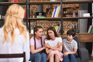 children cheering up depressed mother on family therapy session by female counselor
