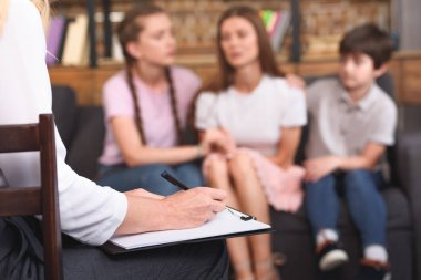cropped image of female counselor writing in clipboard while children cheering up depressed mother on therapy session