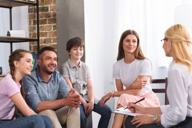 happy family sitting on therapy session by female counselor writing in clipboard in office