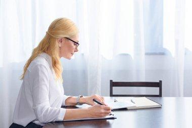side view of female psychiatrist in eyeglasses looking at digital tablet screen at table in office