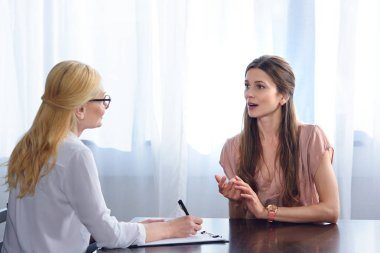 woman gesturing by hands and talking to female counselor while she writing in clipboard at table in office