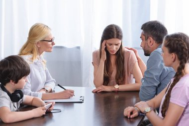 female counselor writing in clipboard while family cheering up woman in office on therapy session