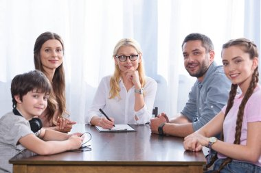 smiling family and female counselor sitting at table on therapy session looking at camera in office