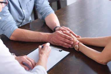 cropped image of couple holding hands of each other while female counselor writing in clipboard at table in office