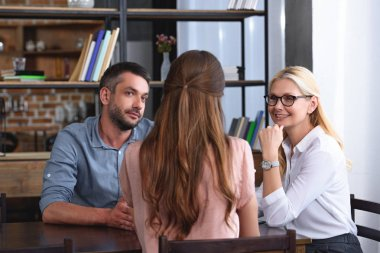couple sitting at table during therapy session by female counselor in her office