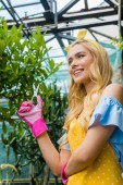 Fotografie low angle view of smiling girl in rubber gloves and apron holding scissors while working in greenhouse