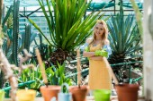Photo beautiful blonde girl in rubber gloves standing with crossed arms and smiling at camera in greenhouse