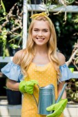Photo young woman in rubber gloves holding watering can and smiling at camera in greenhouse