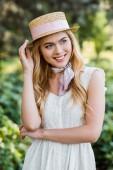 Fényképek gyönyörű pályázati szőke lány ruha és fonott kalap szalaggal, és mosolyogva néz el a parkban